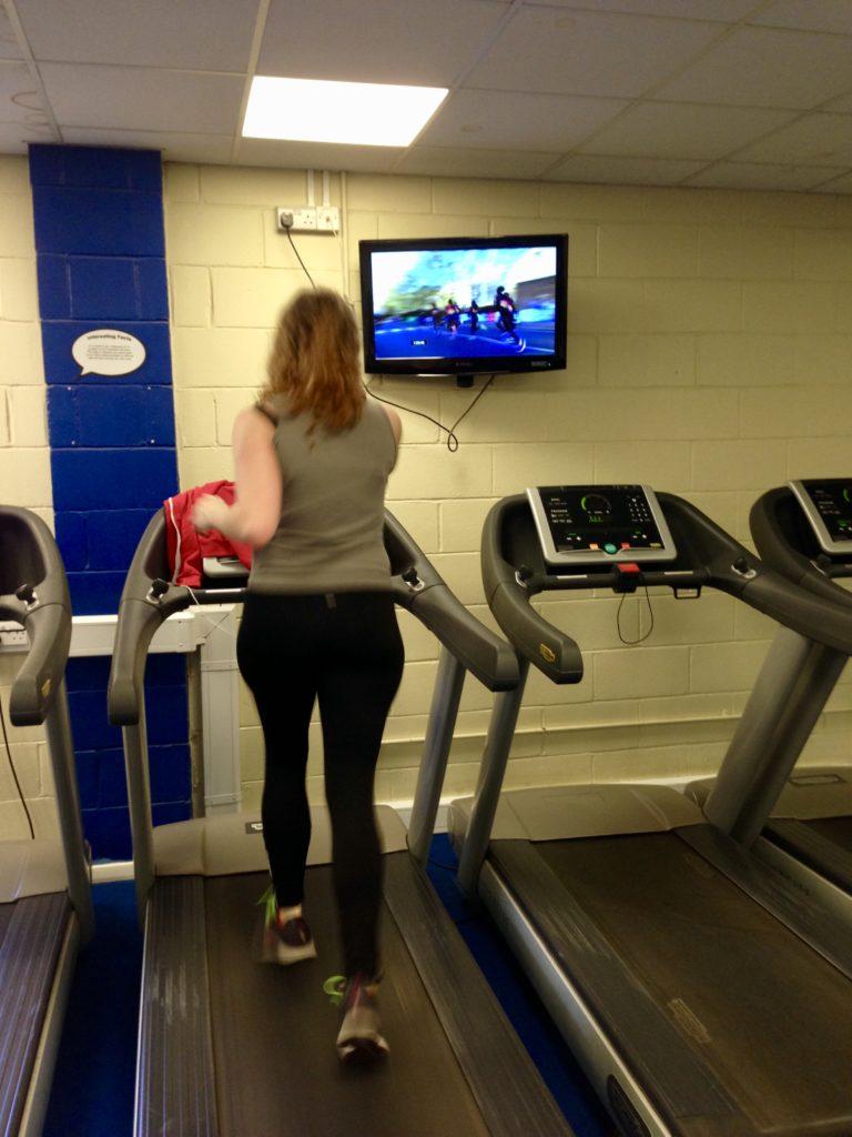 Záběr z posilovny jak běžím a sleduji živě maraton v Londýně