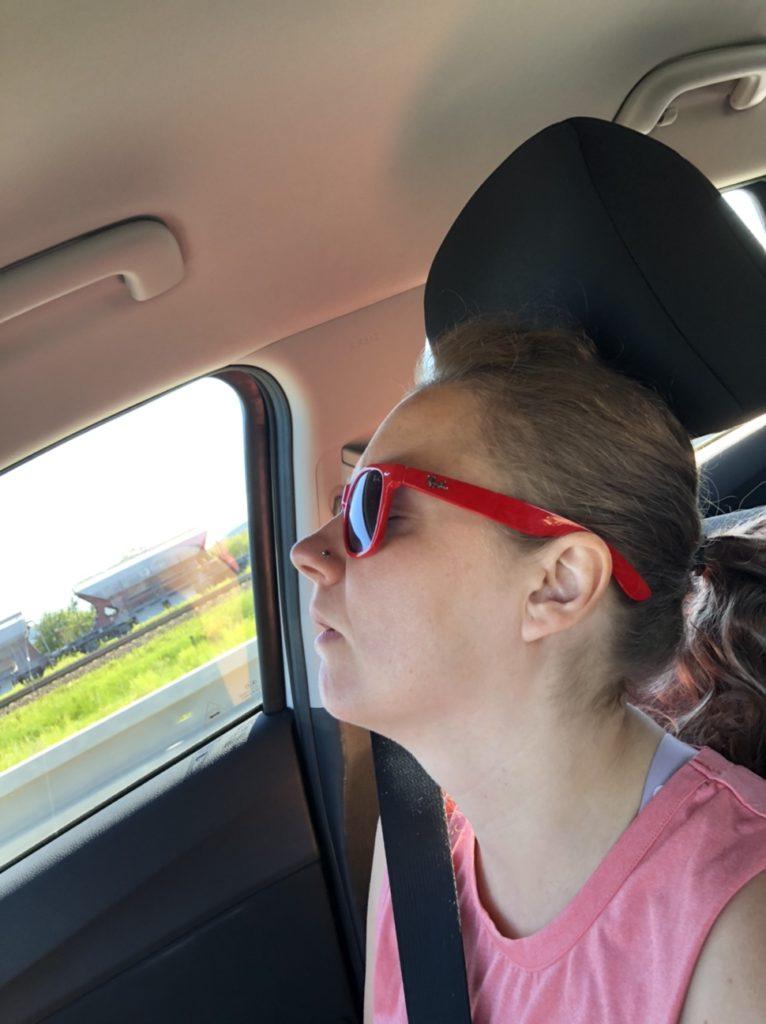 Záběr na spící Aničku v autě